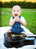 Little boy with a guitar on the grass — Stock Photo
