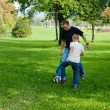 Young boy playing football with his father — Stock Photo #13102513