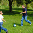 Young boy playing football with his father — Stock Photo #13102532