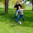 Foto Stock: Young boy playing football with his father