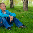 Young boy sitting outdoors — Stock Photo #13103180