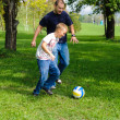 Young boy playing football with his father — Stock Photo