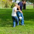 Young boy playing football with his father — Stock Photo #13104012