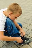 Niño atar los cordones — Foto de Stock