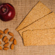 Red apple with crispbread and almonds — Stock Photo