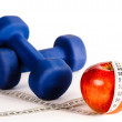 Blue dumbbells and red apple with measure tape — Stock Photo