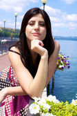 Heppy female model posing in front of flowers on a italian lake — Stock Photo