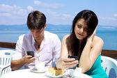 Paar texting ontbijten tegenover meer — Stockfoto