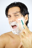 Man shouting while shaving cutting with blade — Stock Photo