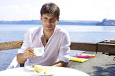 Handsome man having breakfast in front of lake in Italy — Stock Photo