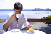 Young handsome man having breakfast on lake reading tablet — Stock Photo