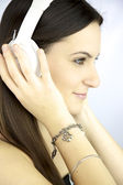 Cute girl listening music with white headphones — Stock Photo