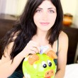 Happy woman putting money in piggy bank — Stock Photo