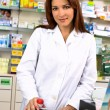 Beautiful happy pharmacist at the desk — Stock Photo