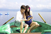 Happy couple smiling on boat watching ipad electronic tablet — Stock Photo