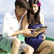 Husband and wife smiling reading email on boat — Stock Photo #26000667
