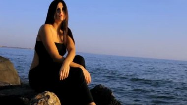 Woman sitting lonely on the beach — Vídeo de stock