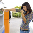 Beautiful brunette punching gas station because of high price — Stock Photo