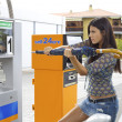 Woman trying to destroy gas station with umbrella — Stock Photo #27462665