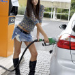 Sexy woman putting gas in car at gasoline station — Stock fotografie