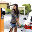 Young woman putting fuel to her car — 图库照片