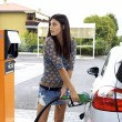 Stock Photo: Young womputting fuel to her car