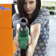 Portrait of female model holding and pointing gas gun — Stock Photo
