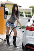 Sexy woman putting gas in car at gasoline station — Stock Photo