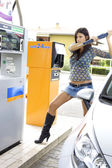 Woman ready to destroy gas station — Stock Photo
