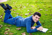 Happy man with tablet in park — Stock Photo
