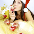 Gorgeous woman santa Claus kissing little christmas toy — Stock Photo