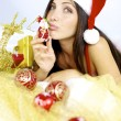Stock Photo: Gorgeous womsantClaus kissing little christmas toy
