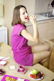 Happy woman eating strawberry for breakfast — Stock Photo