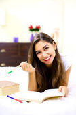 Cute young woman studying in bed at home — Stock Photo