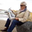 Happy elder man reading newspaper on the beach — Stock Photo