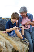 Child having fun with grandmother with tablet outdoors — Stock Photo