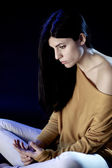 Sad woman sitting in the dark thinking — Stock Photo