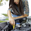 Stock Photo: Young womtrying to fix engine of broken car