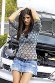 Desperate female model in front of broken car — Stock Photo