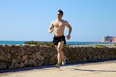 Cool muscular man running on street — Stock Photo