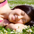 Happy chinese american girl smiling and relaxing laying in grass with flowers — Stock Photo #43957335