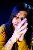 Woman praying for mercy after violence — Stock Photo