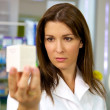 Portrait of doctor holding medicine in pharmacy — Stock Photo