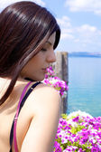Woman relaxing in vacation in front of lake and flowers — Stock Photo