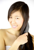 Happy Chinese girl brushing long hair — Stockfoto