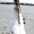 Gorgeous lady on the beach dancing with white dress — Stock Photo #48944715