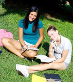 Smiling happy female students in college with books — Stock Photo