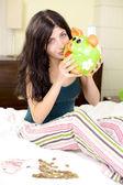Happy woman hugging piggy bank full of money — Stockfoto