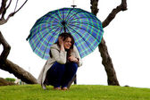 Beautiful woman with umbrella sitting scared of coming storm — Stock Photo