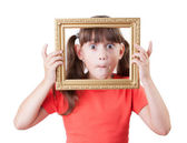 Little girl holding a frame for pictures — Stock Photo